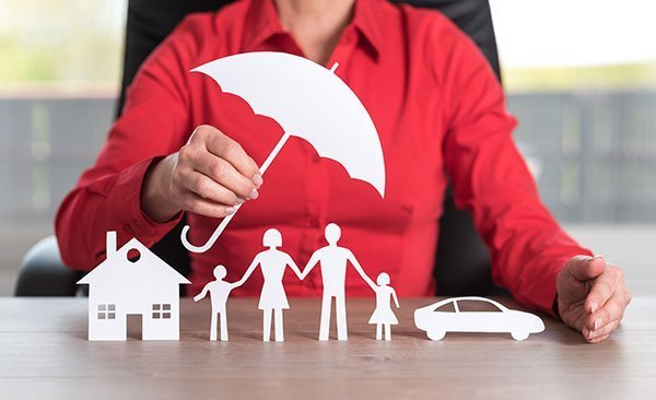 Asset Protection concept: attorney holding a paper umbrella over paper cut outs representing a family estate