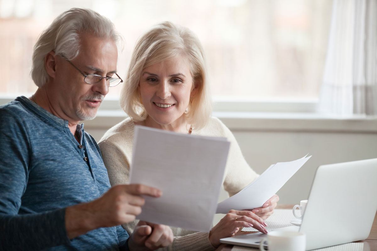Happy older aged couple holding reading their estate plan